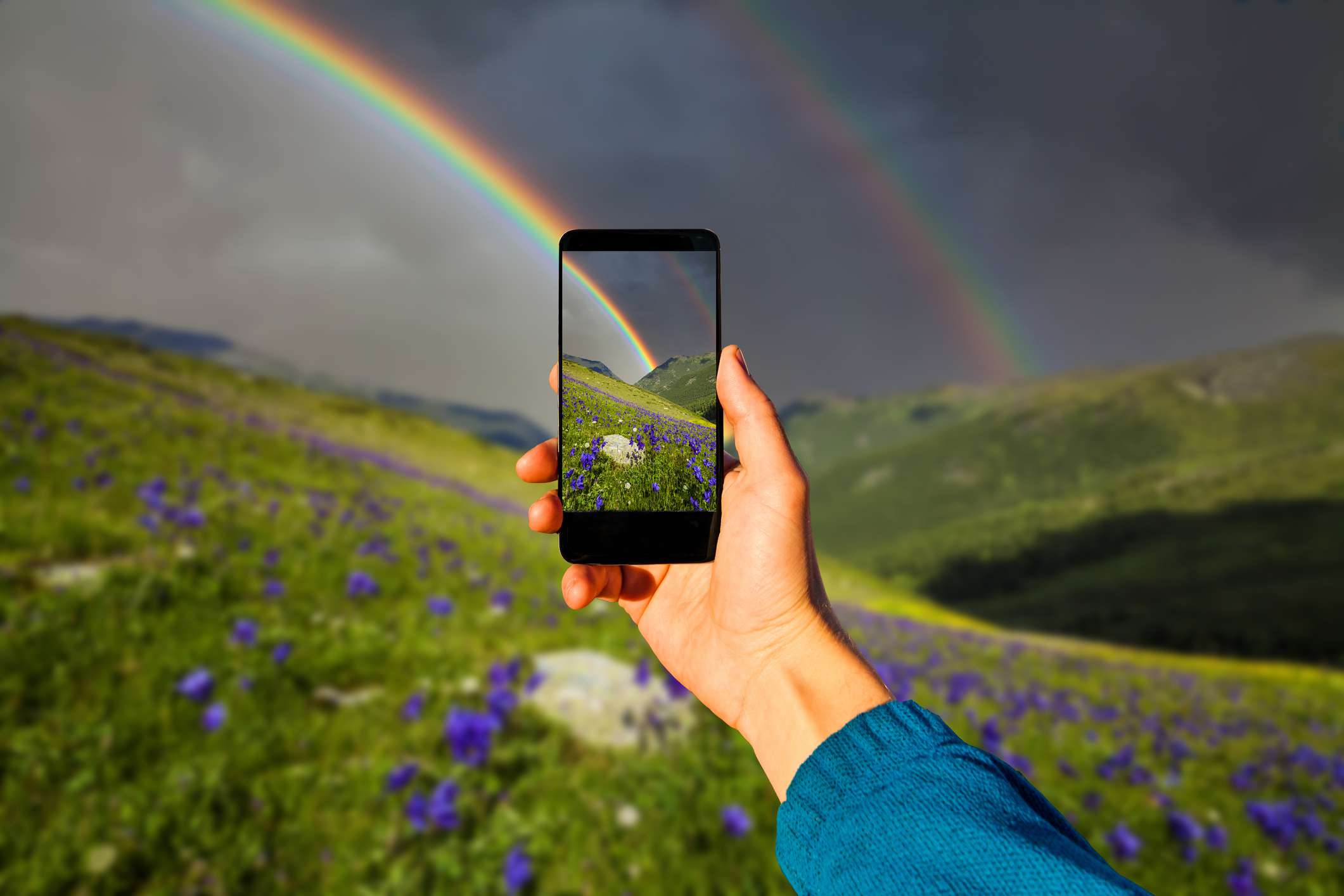 Someone taking a photo of a rainbow against dark clouds on a smartphone.