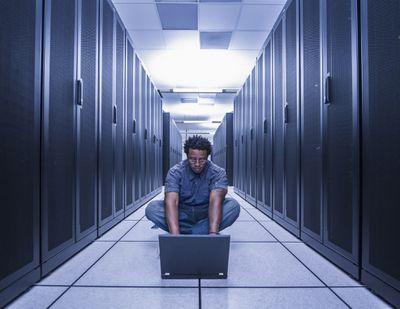 Man using computer in walkway between servers