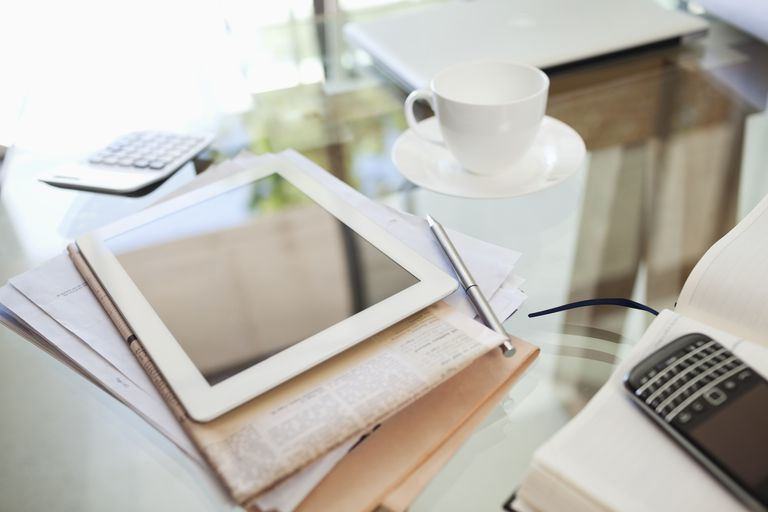 Tablet computer, newspaper, coffee cup and cell phone on desk