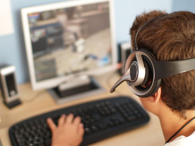 Teenager playing a video game while wearing a gaming headset