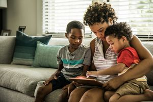 A mother and two kids using an iPad on the couch