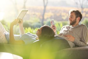 A man on an iphone and a woman using an iPad relaxing outdoors