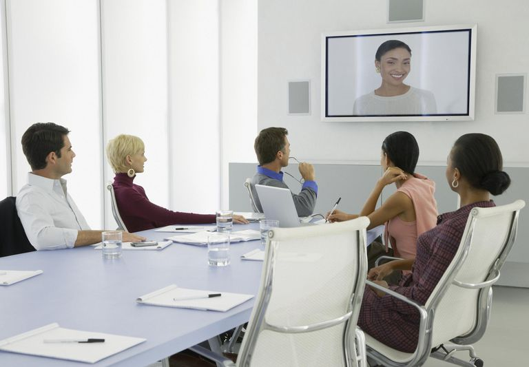 Meeting with people in conference room talking to colleague on Skype on big screenhaving a video conference