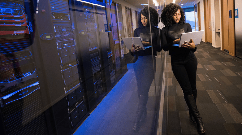 Someone leaning on a a glass wall enclosing a server room while working on a laptop computer.