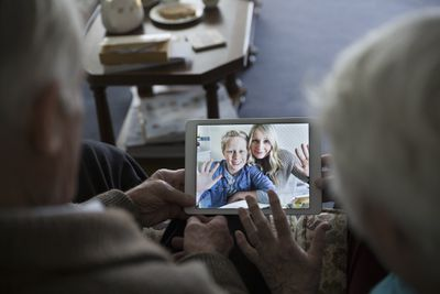 Grandparents using video chat, facetime, skype service to talk to a mother and son