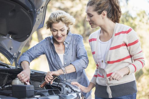 Two women jumpstarting a car battery