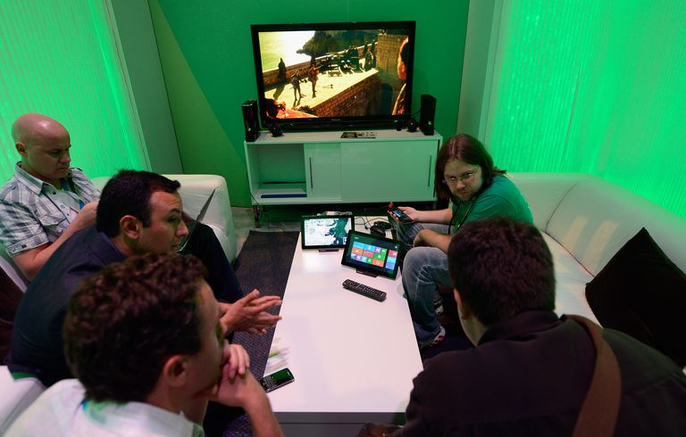 Men playing video games in a green room