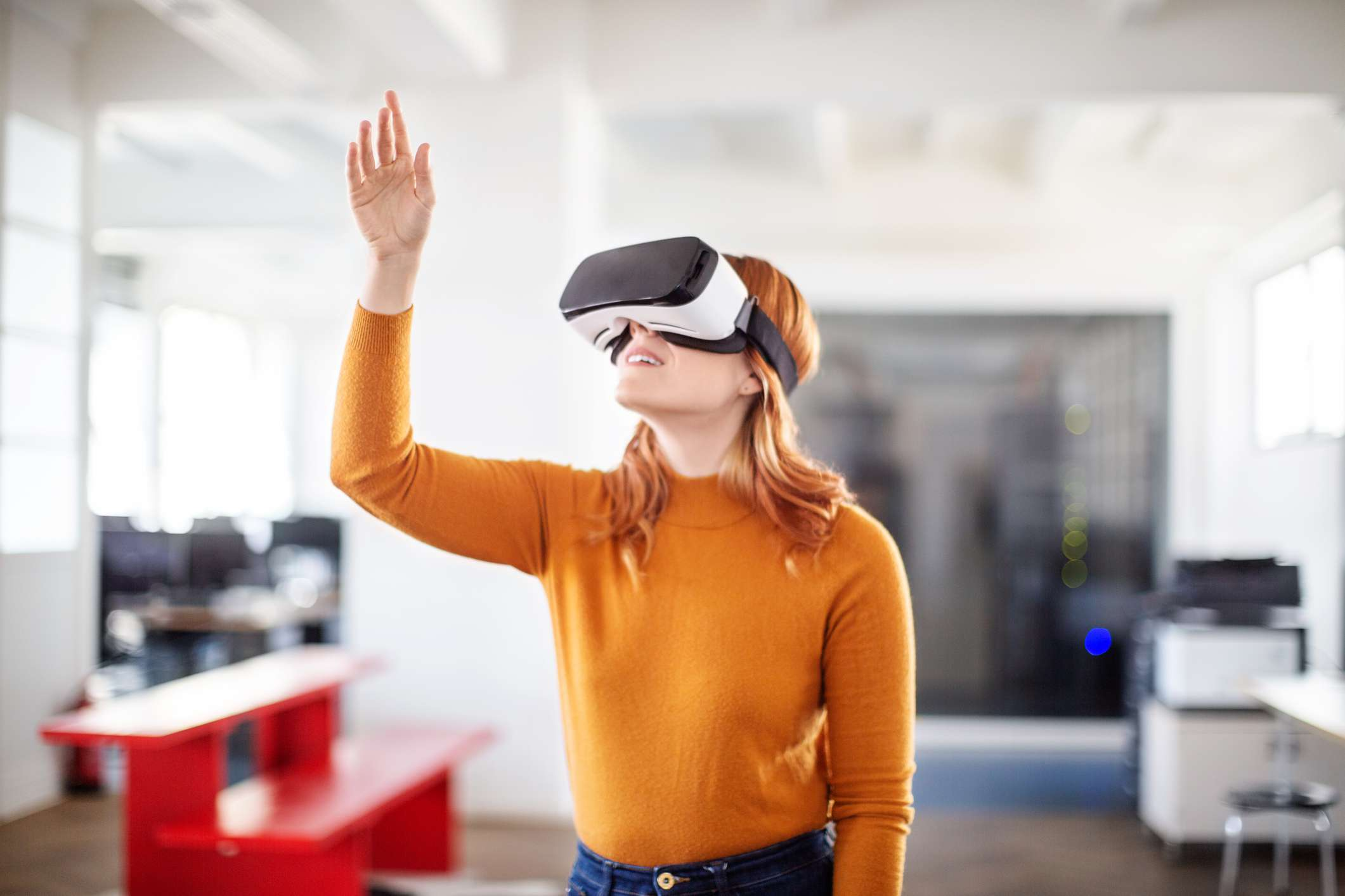 woman wearing VR goggles and reaching up towards something