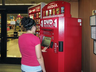 woman getting DVD from RedBox kiosk