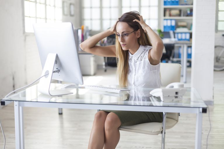 A woman getting a headache from her computer