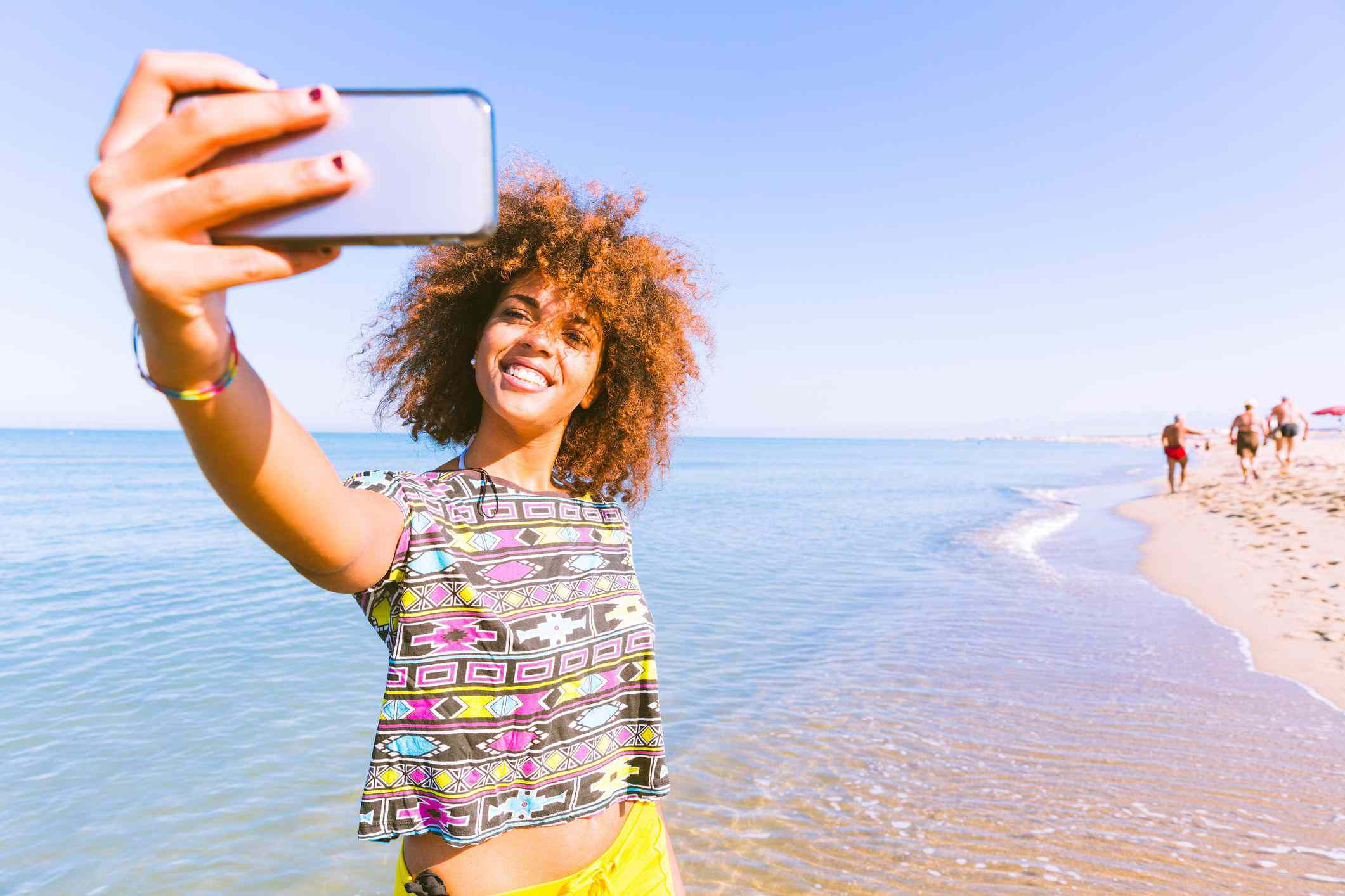 A tourist taking a selfie on the shore at the ocean