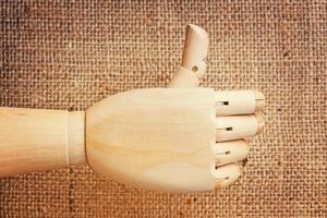 A wooden hand with articulated joints gives a thumbs up. Burlap background.