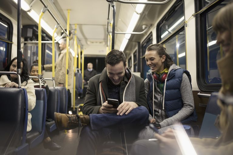 Smiling young couple commuters texting with smart phone on bus
