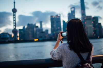 Asian woman taking phone picture of Pudong skyline in the night,Shanghai