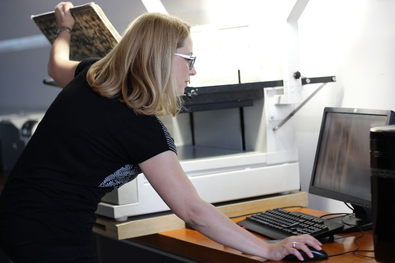 Woman scanning historic newspaper into OCR program