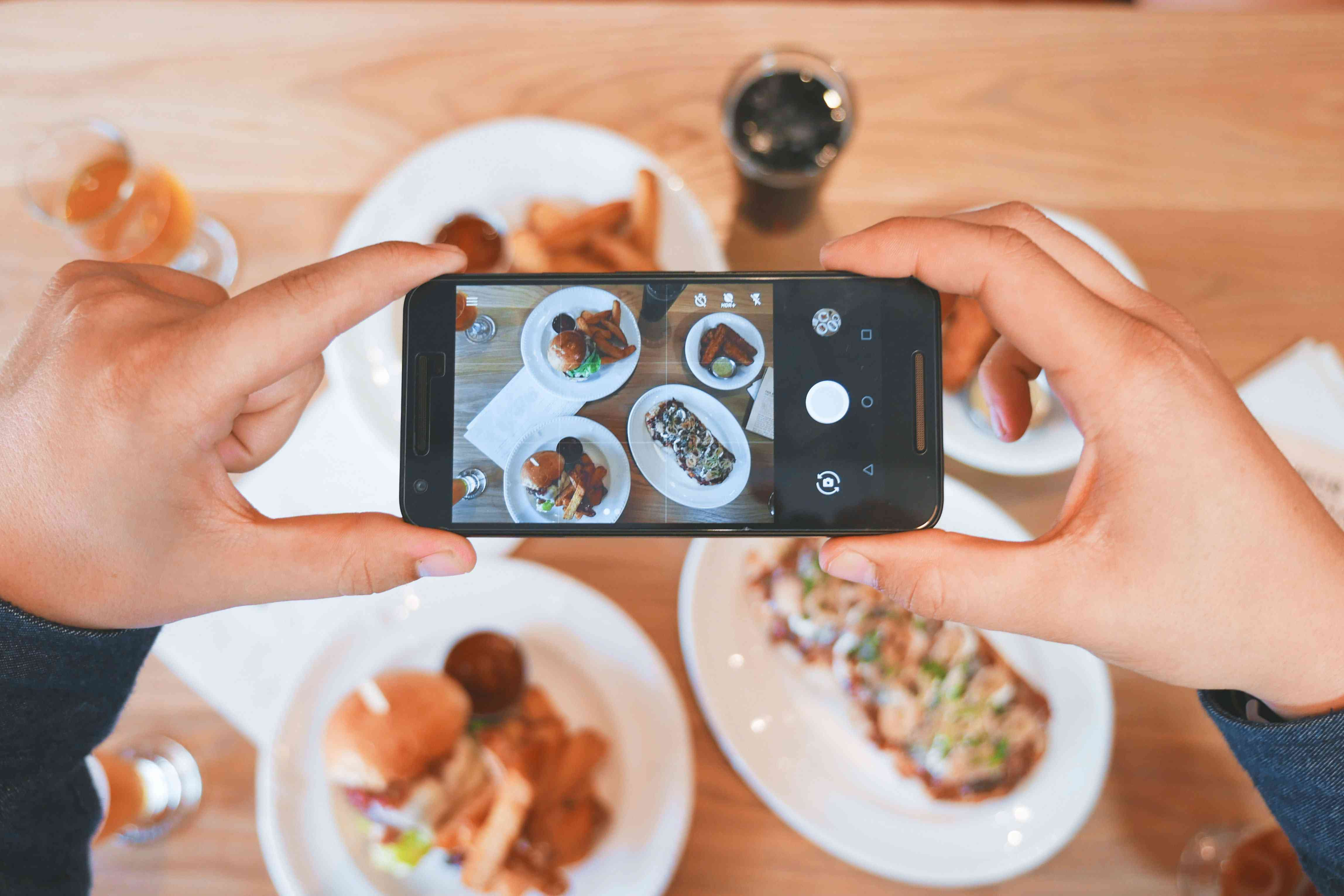 Someone taking pictures of their food with a smartphone.