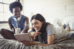 Two friends sitting on a bed, reading on an iPad