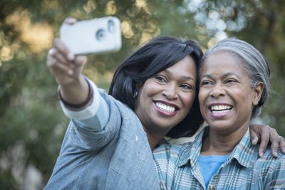 Adult daughter and mother taking selfie on smartphone outside in nature