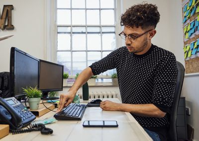 A man sitting at a computer desk and cleaning a black mechanical keyboard.