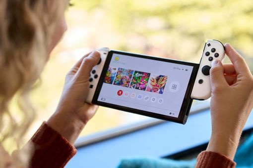 The Nintendo Switch OLED with Joy-Con being attached.
