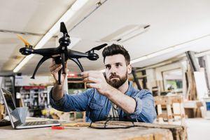 Young man examining drone