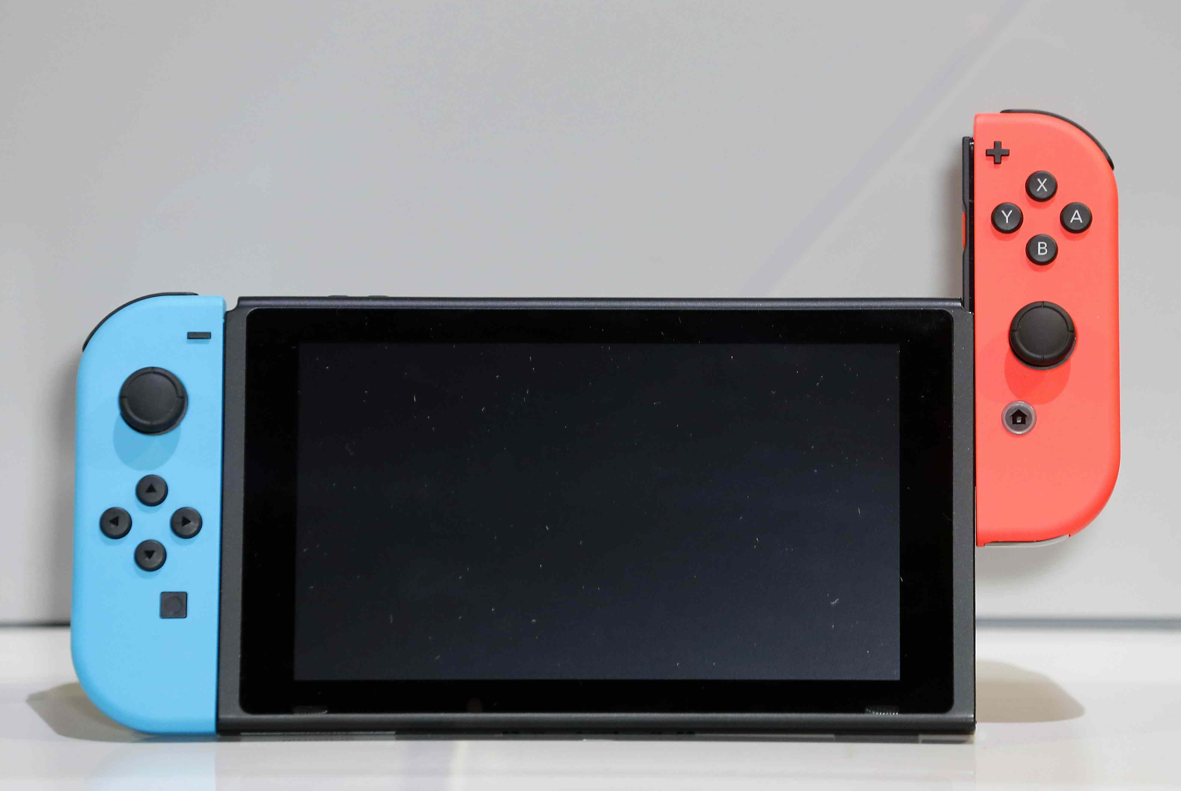 A Nintendo Switch controller is displayed with one side half attached to the screen.