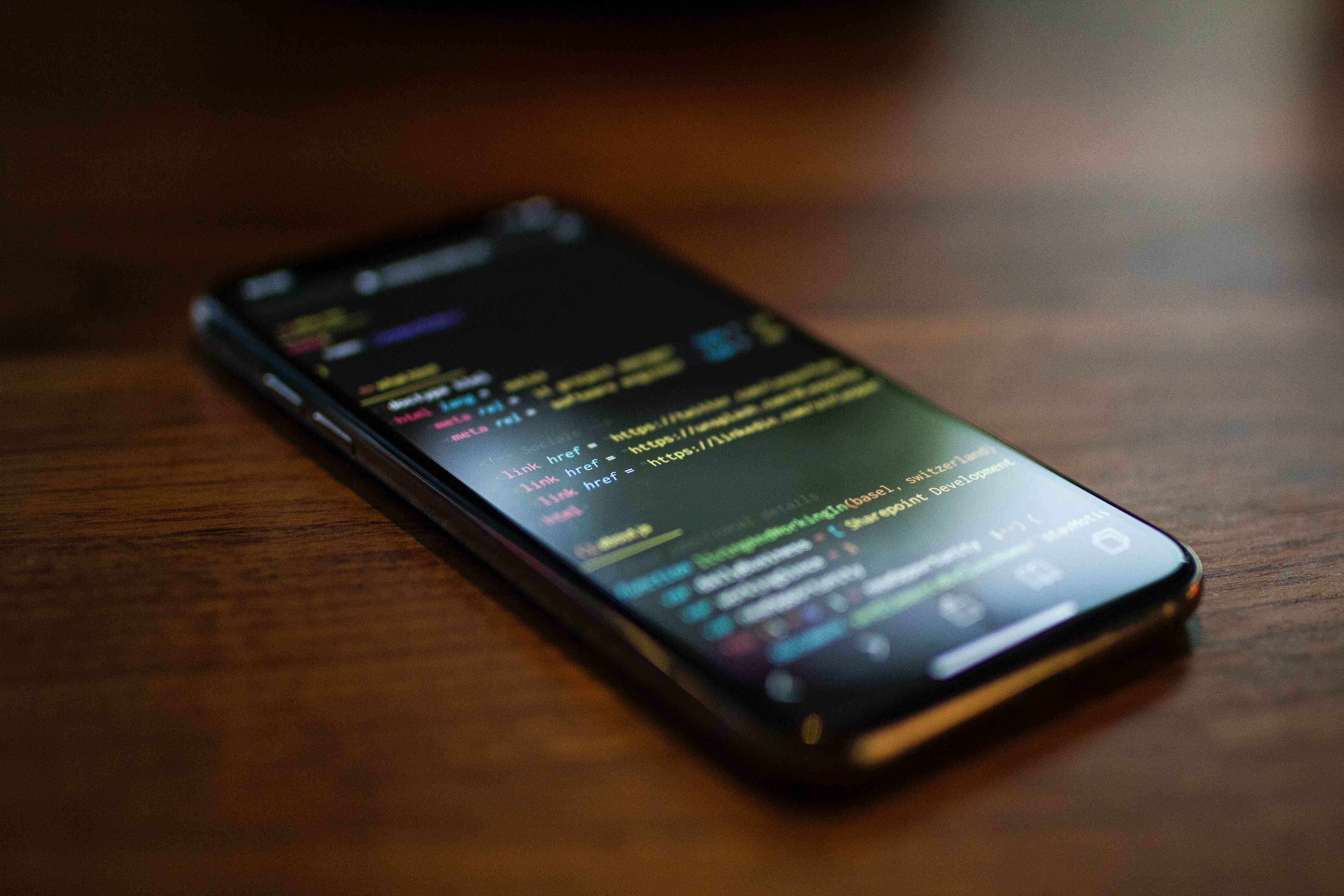 A smartphone with code displayed on the screen sitting on a wooden surface.