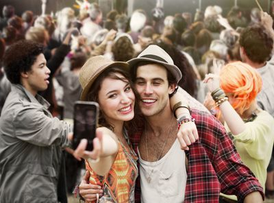 Couple taking self-portrait at music festival
