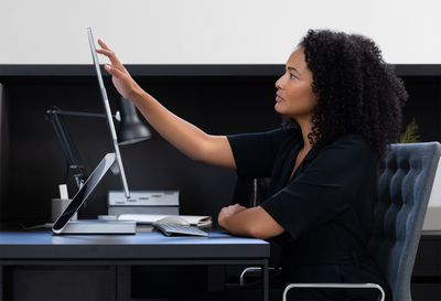 A woman in an office touching the screen of a Microsoft Surface Studio running Windows 11.