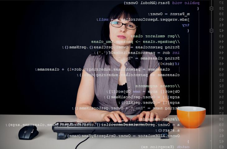 Woman typing on computer with code showing in front of her