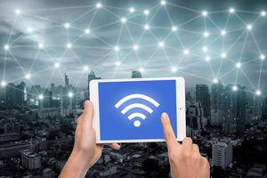 Hand holding tablet with Wi-Fi icon on city and network connection concept. Bangkok smart city and wireless communication network, abstract image visual, internet of things.