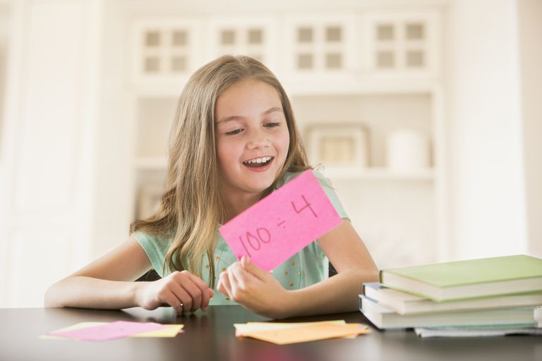 A young girl holding up a hand-written flash card.