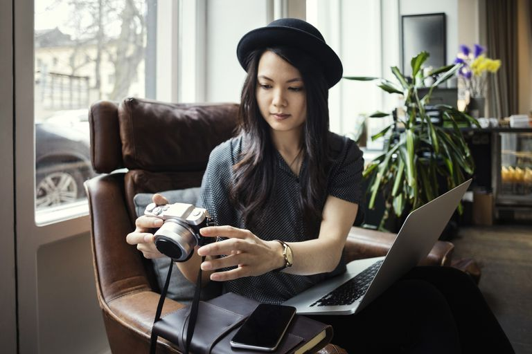 Female entrepreneur holding camera while sitting with laptop on chair