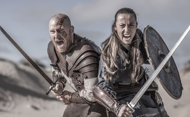 Male and female viking warrior couple in wild highland countryside