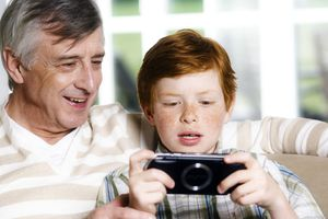 A grandparent and grandchild, with the child playing with a portable video game.