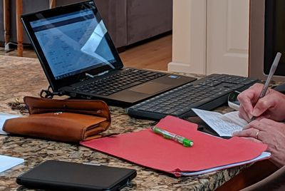 A woman balancing her checkbook while using a spreadsheet.