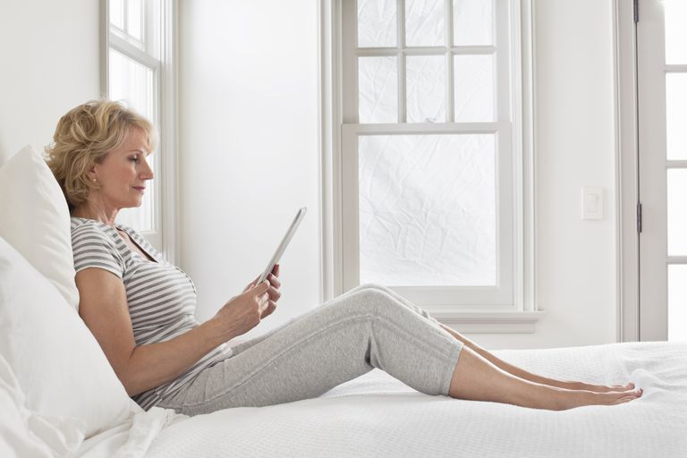 A woman in bed using an iPad
