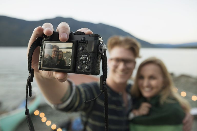 Couple taking a selfie with a digital camera at a waterfront