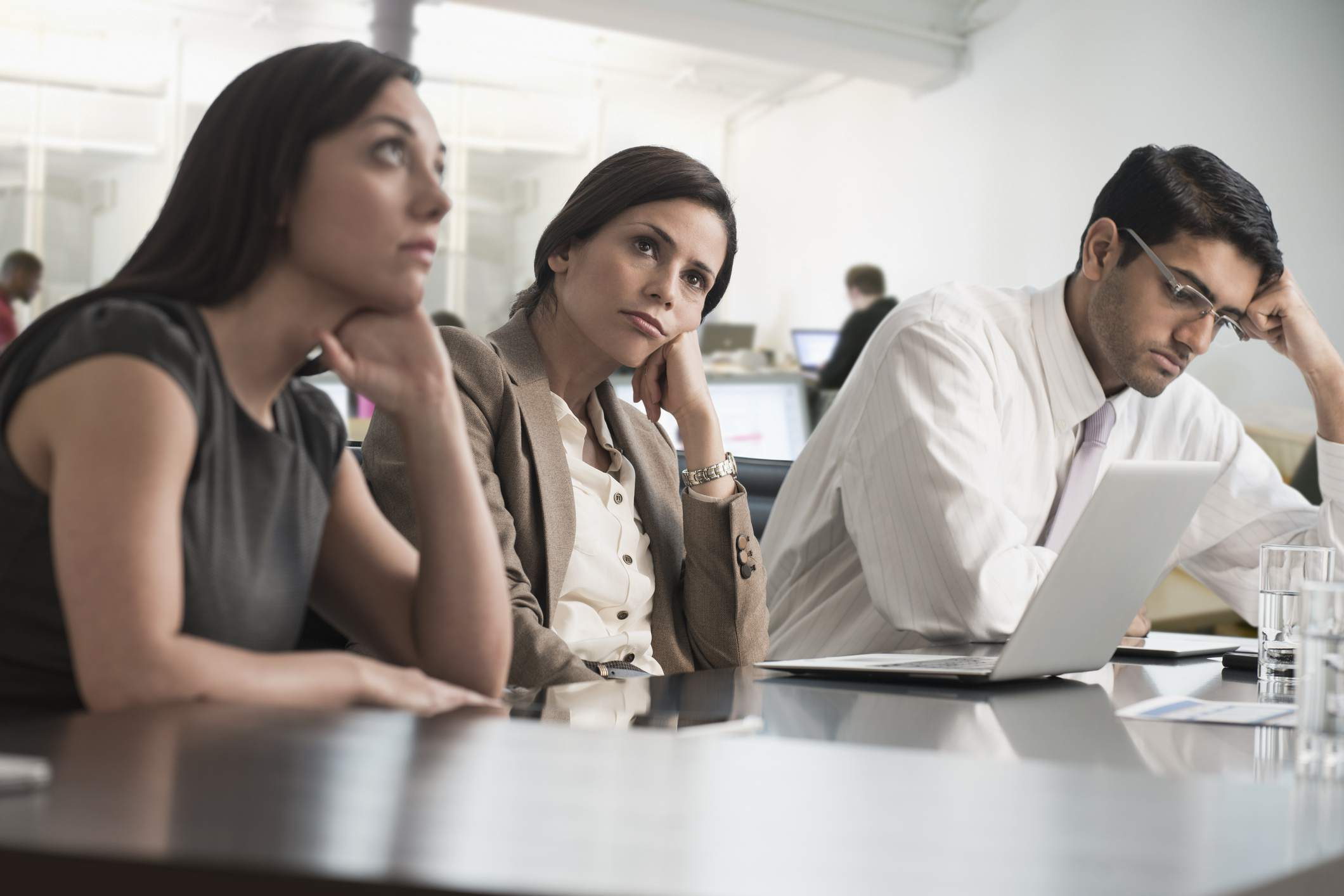 Group of people bored, sitting at a work table