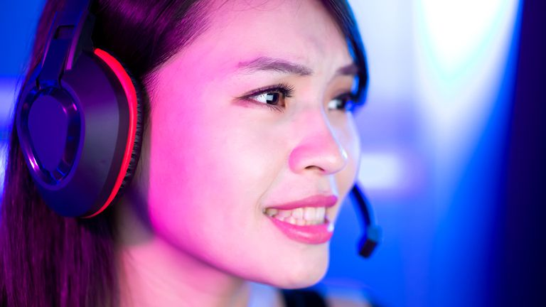 Woman wearing a gaming headset with a mic while playing a video game on an Xbox One.