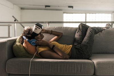 Someone laying on a sofa using a VR system and headphones.