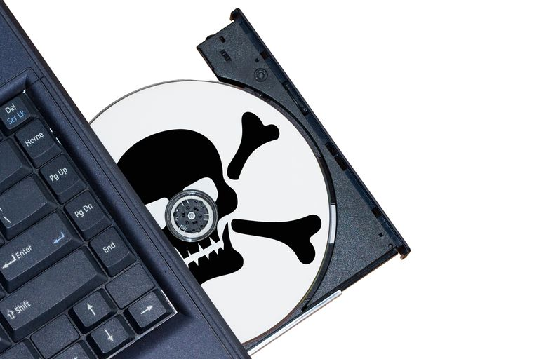 Photo of a CD being loaded into a computer with a skull and crossbones on it