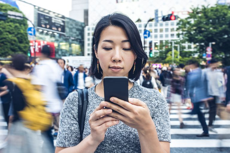 Woman checking iphone on busy street