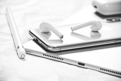 Closeup of AirPods laying on top of an iPhone with the charging case and an Apple Pencil in the bakground.