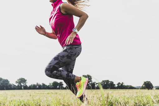 Woman running outdoors with an Apple Watch