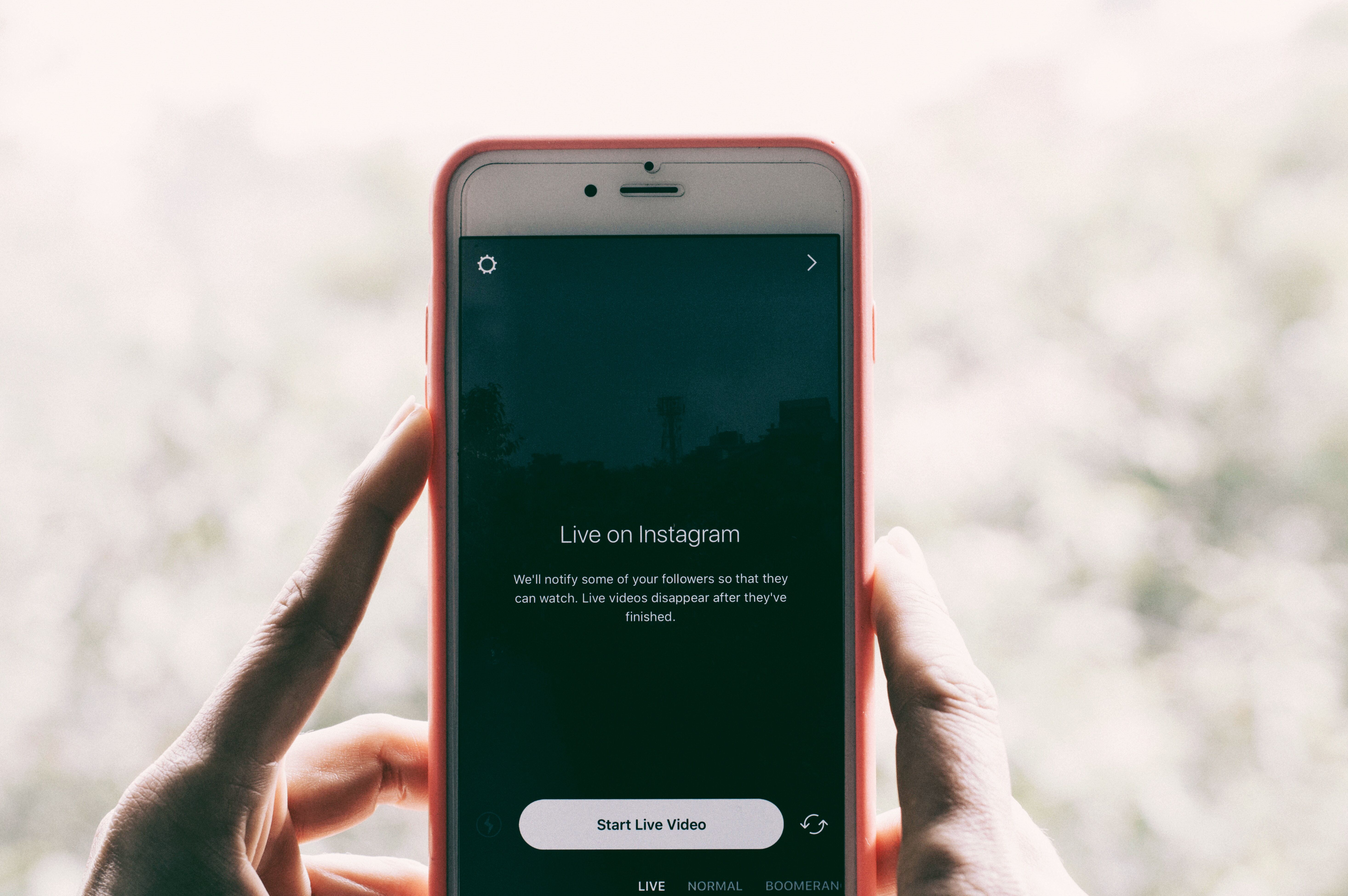 A person holding up a smartphone and getting ready to go live on Instagram