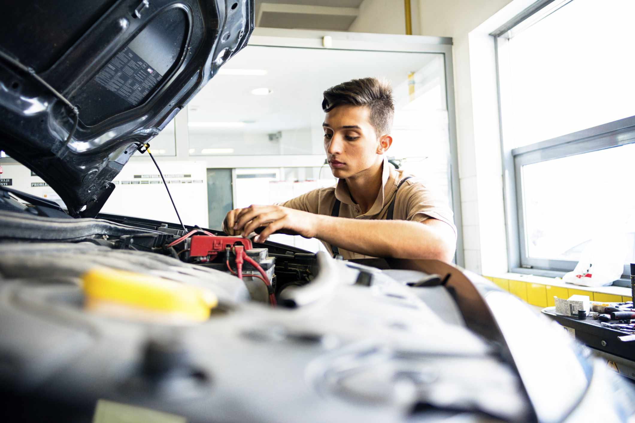 Person working on a car battery
