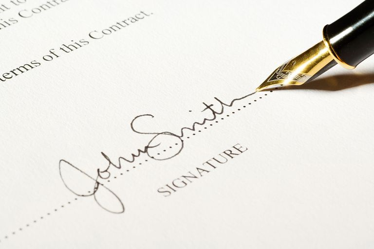 John Smith signing his name with a fountain pen