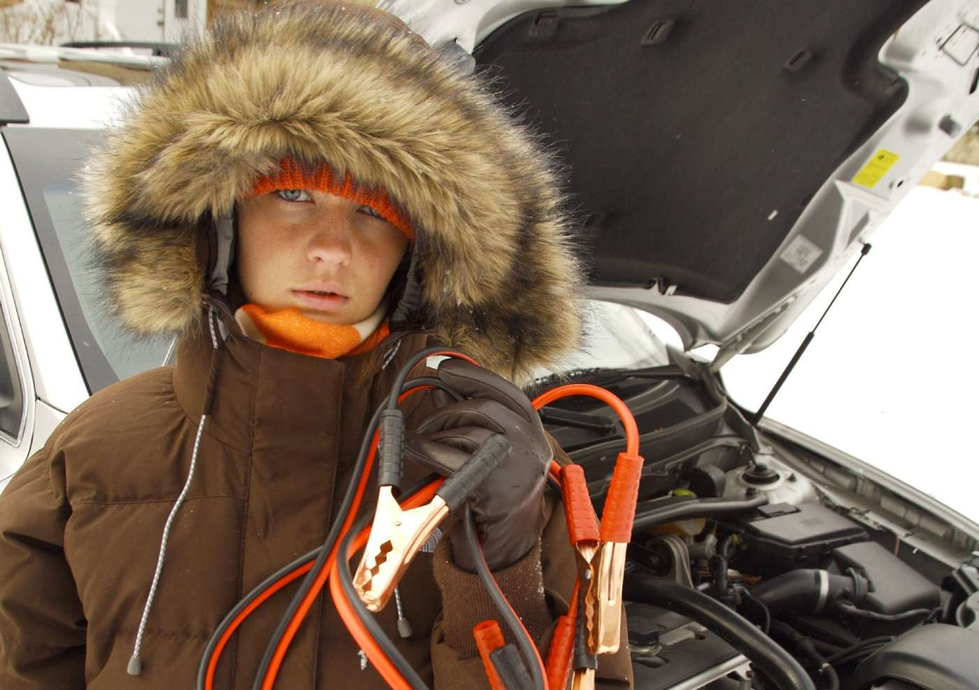 A person in a big winter coat holding up jumper cables in front of a car with its hood open.