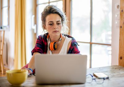 A woman with orange headphones around her neck looking at a Windows 11 laptop.